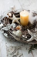 Willow wreath with ornaments shaped like marine animals and lit candle