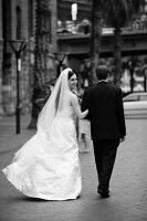 Bride wearing long white dress and groom in black suit walking down the street (black and white photo)