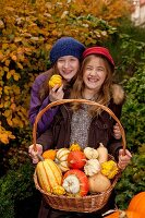 Two girls holding a basket with a variety of squash in the garden
