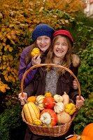 Zwei Mädchen halten einen Korb mit verschiedenen Kürbissen im Garten