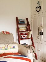 White fitted cupboards and a wooden ladder holding books, next to a sofa