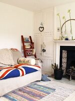 Sofa with Union Jack seat cushions and wooden ladder with books next to a white built-in cupboard