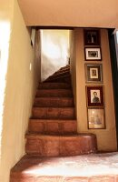 Photo gallery on the wall next to a stairway in an Ecuadorian manor house