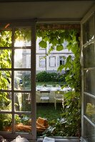View out a window of a set table in a garden; in the background a partial view of the main building