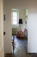 Chair upholstered with floral fabric next to a floor lamp in a guest room with wooden flooring in a former monastery