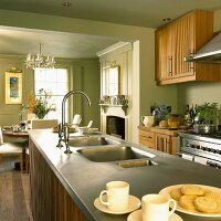 Country home style kitchen with pastel green walls, wooden cabinets, open fireplace and dining area