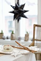 Advent crafting with white paper stars and cinnamon sticks on table; black, star-shaped lampshade in background