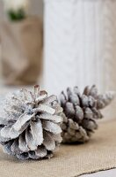 Timeless Christmas table decoration of fir cones sprayed white on ecru linen runner