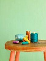 Bunte Garnrollen auf Vintage-Hocker vor grüner Wand