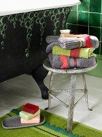 Metallhocker im Vintagelook mit Handtuchstapel; daneben eine freistehende, grüne Badewanne mit aufgemaltem Seifenblasenmuster
