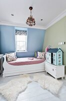 Cheerful child's bedroom with large dolls' house and soft animal-skin rugs on floor next to bed