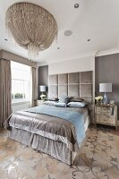 Lavish, silver double bed with tall, velvet-covered headboard below magnificent, modern chandelier