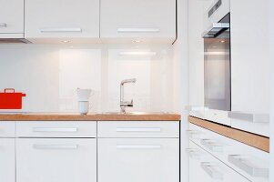 Kitchen with white furnishings, wooden worksurface and fitted cooker