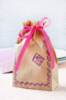 Paper gift bag with ribbon and pattern made using hand-carved rubber stamps