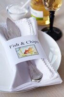 Napkin ring with lettering reading Fish & Chips and decorated with postage stamps