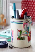 Tin can decorated with postage stamps with bird motifs used as pen holder