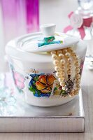 China jar decorated with postage stamps and used as jewellery box