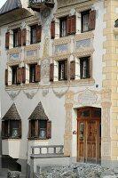 Verzierte Fassade eines mehrstöckigen Gebäudes in Val Sinestra im Kanton Graubünden, Schweiz