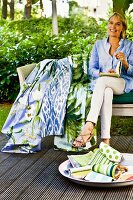 Woman sitting on bench on terrace with colourful fabric samples