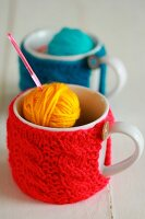 Mugs with knitted covers, balls of wool and crochet needle