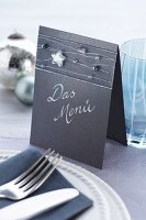 Menu made from folded cardboard decorated with ribbon and beads threaded on silver wire