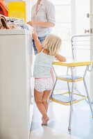 Little girl reaching for cornflake box in kitchen with mother