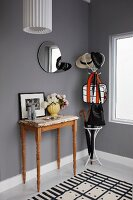Cloakroom in cool black, white and grey colour scheme relieved by vintage-effect console table