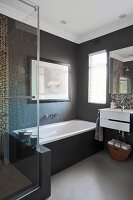 Dark, plain walls in bathtub area and mosaic tiles above sink and in shower cabinet behind glass door