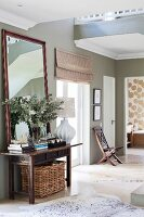 Antique console table and mirror against wall painted olive green and animal-skin rugs on floor