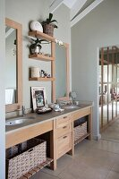 Long washstand with solid wood base unit and storage baskets in open-plan bathroom