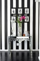 Various vases on chromed metal table below gallery of framed photos on black and white striped wall