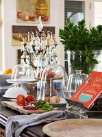 Vegetables on chopping board and various dishes with glass covers next to cookery book on kitchen counter