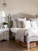 Pale grey antique bed with headboard and carved ornamentation next to bedside table and table lamp