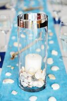 Maritime table decoration: shells in candle lantern