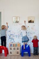 Three children scribbling on a white wall with framed photographs, plastic chairs and dolls' house