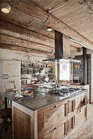 Rustic island counter with stainless steel extractor hood in open-plan interior of wooden chalet