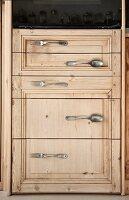 Cupboard door with handles made from vintage cutlery