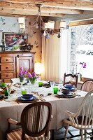 Set table in corner of rustic living room in front of partially visible panoramic window