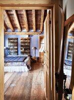 View through open door into rustic bedroom with wooden floor