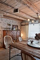 Table with rustic wooden top and vintage chairs in living room with wood-beamed ceiling