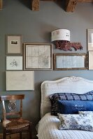 Scatter cushions on French bed with curved headboard below framed pictures on pale grey wall