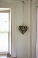 Decorative heart hanging in corner of room next to window