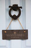 Do not disturb sign hanging on metal door knocker