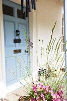 Entrance area with blue door, wind chimes & plant arrangement