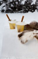 Hot apple punch with pear liqueur next to fur in snow