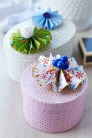 Colourful paper flowers with buttons as centres decorating various gift boxes