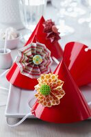 Colourful paper flowers decorating red party hats