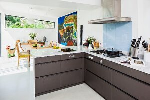 Angular, open-plan fitted kitchen with grey brown fronts and pale, engineered stone worksurface; view of dining table and large, Aboriginal painting