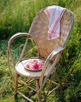 Teller mit Rosenblüten auf Korbstuhl in der Wiese