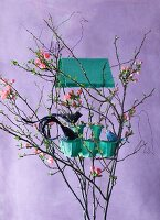 Bird house made from egg carton in Easter arrangement of twigs